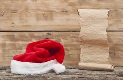 圣诞老人帽子和老纸纸卷 库存照片