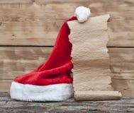 圣诞老人帽子和老纸纸卷 免版税库存图片