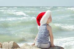 圣诞老人帽子和镶边T恤杉的男孩坐海滩 回到视图 免版税库存照片