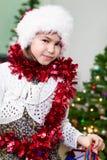 圣诞老人帽子和闪亮金属片的,画象可爱的青春期前的白种人女孩,看照相机 免版税库存图片