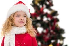 圣诞老人帽子和围巾的欢乐的小女孩 图库摄影