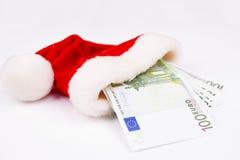圣诞老人帽子和货币 库存图片