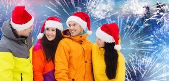 圣诞老人帽子和滑雪服的愉快的朋友户外 图库摄影