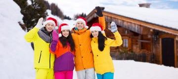 圣诞老人帽子和滑雪服的愉快的朋友户外 库存图片