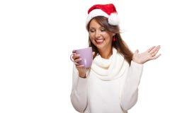 圣诞老人帽子啜饮的咖啡茶的冷的少妇 免版税库存图片