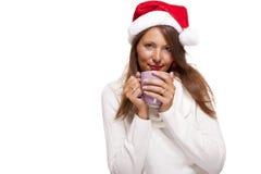 圣诞老人帽子啜饮的咖啡茶的冷的少妇 库存图片