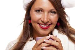 圣诞老人帽子啜饮的咖啡茶的冷的少妇 免版税库存照片