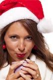 圣诞老人帽子啜饮的咖啡茶的冷的少妇 图库摄影