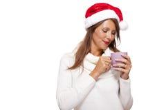 圣诞老人帽子啜饮的咖啡茶的冷的少妇 库存照片
