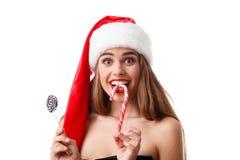 圣诞老人帽子尖酸的圣诞节糖果的愉快的女孩 查出在白色 免版税库存照片