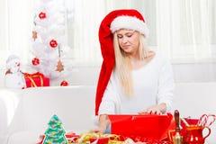 圣诞老人帽子开头圣诞节礼物的妇女 免版税库存图片
