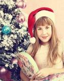 圣诞老人帽子开放当前箱子的青春期前的白肤金发的女孩 免版税库存照片