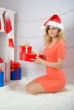 圣诞老人帽子开头圣诞节礼物的女孩 免版税库存照片