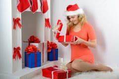 圣诞老人帽子开头圣诞节礼物的女孩 库存图片