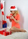 圣诞老人帽子开头圣诞节礼物的女孩 库存照片