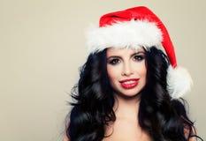 圣诞老人帽子微笑的美丽的圣诞节妇女 库存照片