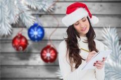 圣诞老人帽子文字的妇女在笔记薄 免版税库存照片