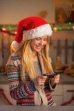 圣诞老人帽子文字sms的微笑的十几岁的女孩在厨房里 图库摄影