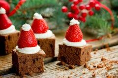 圣诞老人帽子果仁巧克力叮咬 图库摄影