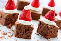 圣诞老人帽子果仁巧克力咬住用草莓和打好的奶油或者c 库存图片