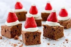 圣诞老人帽子果仁巧克力咬住用草莓和打好的奶油或者c 库存照片