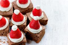 圣诞老人帽子果仁巧克力咬住用草莓和打好的奶油或者c 免版税图库摄影