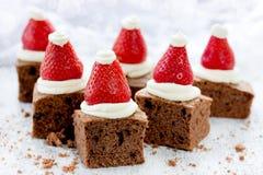 圣诞老人帽子果仁巧克力咬住用草莓和打好的奶油或者c 免版税库存图片