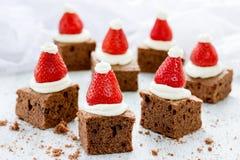 圣诞老人帽子果仁巧克力咬住用草莓和打好的奶油或者f 免版税库存照片