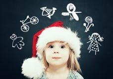 圣诞老人帽子梦想的小女孩在礼物 圣诞节孩子 库存照片