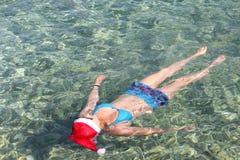 圣诞老人帽子游泳的妇女在海 图库摄影