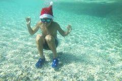 圣诞老人帽子游泳的男孩在海 免版税图库摄影