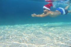 圣诞老人帽子游泳的男孩在海 库存照片