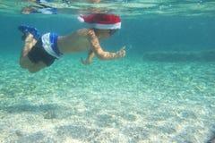 圣诞老人帽子游泳的男孩在海 免版税库存照片