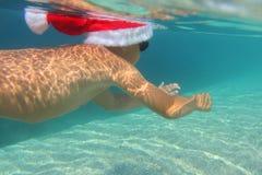 圣诞老人帽子游泳的男孩在海 库存图片