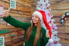 圣诞老人帽子的一个女孩在圣诞树的背景做selfie 免版税库存图片