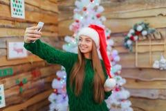 圣诞老人帽子的一个女孩在圣诞树的背景做selfie 免版税图库摄影