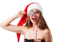 圣诞老人帽子的一个愉快的女孩拿着两个圣诞节糖果,并且他们中的一个闭上眼睛和快乐微笑 查出 免版税库存照片