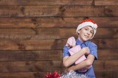 圣诞老人帽子的一个白被剥皮的欧洲少年看照相机并且拥抱一件新年` s礼物 免版税库存图片