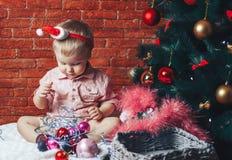 圣诞老人帽子的一个美丽的婴孩在与圣诞节玩具和光的一棵圣诞树附近坐 库存照片