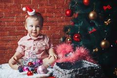 圣诞老人帽子的一个美丽的婴孩在与圣诞节玩具和光的一棵圣诞树附近坐 免版税库存照片
