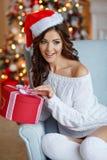 圣诞老人帽子的一个美丽的苗条深色的女孩在舒适坐 免版税图库摄影