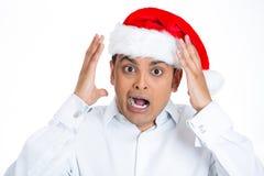 圣诞老人帽子的一个震惊和被注重的年轻人 免版税图库摄影