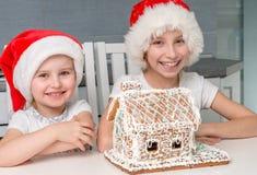 圣诞老人帽子的两个微笑的姐妹有乳脂状的饼干房子的 库存图片