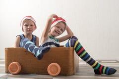 圣诞老人帽子的两个滑稽的男孩使用与在纸板画的马 人在家获得乐趣 圣诞节假日conce 图库摄影