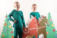 圣诞老人帽子的两个滑稽的男孩使用与在纸板画的马 人在家获得乐趣 圣诞节假日conce 免版税库存照片