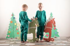 圣诞老人帽子的两个滑稽的男孩使用与在纸板画的马 人在家获得乐趣 圣诞节假日conce 免版税库存图片