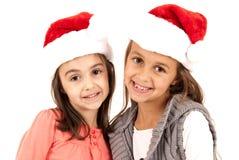 戴圣诞老人帽子的两个年轻可爱的姐妹 免版税库存照片
