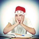 圣诞老人帽子的乏味学生 免版税库存图片
