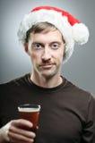 戴圣诞老人帽子的人勉强地敬酒用啤酒 库存照片