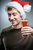戴圣诞老人帽子的人勉强地敬酒用啤酒 库存图片